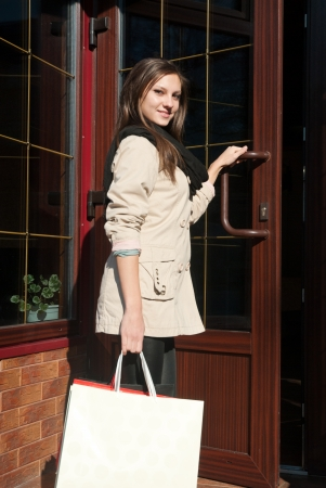 Young pretty woman entering shop photo