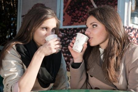mujer tomando cafe: Dos mujeres tomando un caf� en llevar y chat Foto de archivo