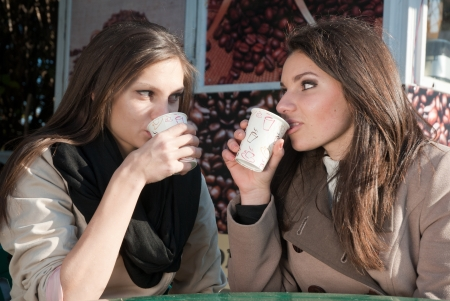 Two women having coffee in take-away and chatting photo