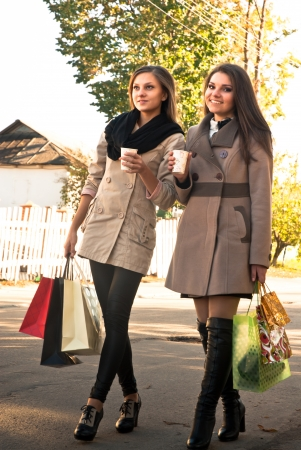 Two happy women walking with shopping bags photo