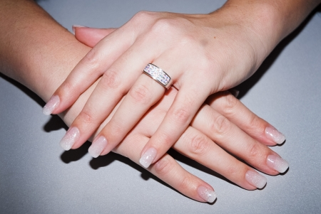 Beautiful hands with fresh manicure and diamond ring photo