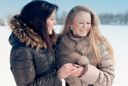 Two happy teen friends laughing outdoors on winter snowy day photo