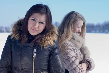 Two unhappy teenage girls on winter day photo