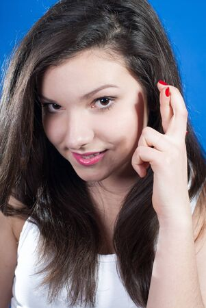 Young woman showing fingers crossed over bluescreen background photo