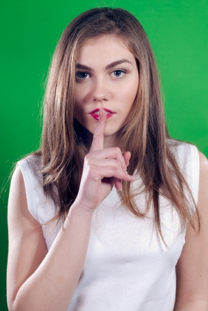 Young beautiful woman showing silence sign over greenscreen background Stock Photo - 17492694