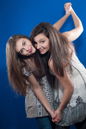 Two happy female teenage friends dancing over bluescreen background photo