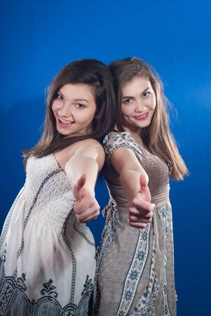 Two happy teenage friends showing thumbs up on blue screen background photo