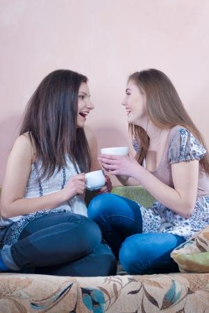 mejores amigas: Dos amigos adolescentes felices bebiendo t� en casa y riendo