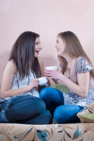 Two happy teenage friends drinking tea at home and laughing
