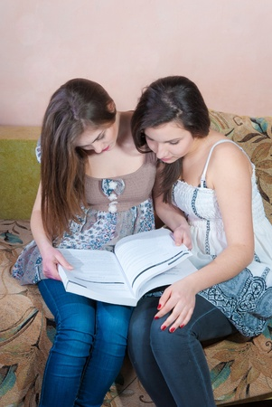 Two teenage girls studying at home with book photo