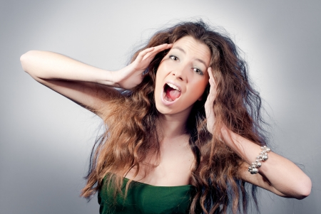 Younf woman with long wavy hair screaming in despair photo
