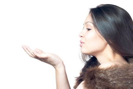 Beautiful young woman in fur coat blowing on empty palm over white background photo