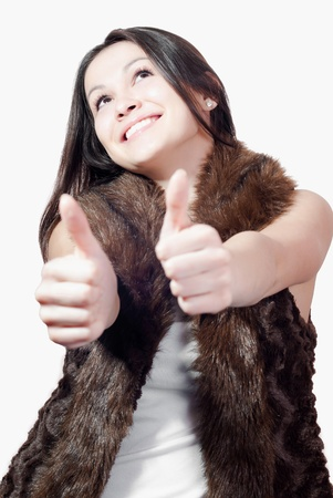 waistcoat: Beautiful young woman in fur coat showing thumbs up over white background