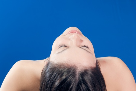 Beautiful young woman lying face up closeup bare shoulders eyes closed over blue background photo