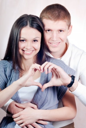 Happy young couple with heart symbol embracing and smiling studio portrait Stockfoto