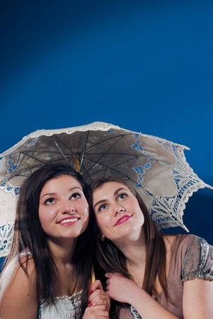 Two happy smiling teenage girls under lace umbrella looking up on empty space blue screen photo