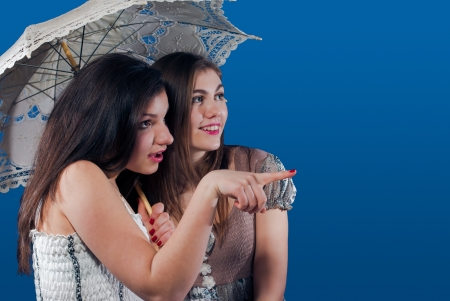 Two happy smiling teenage girls under lace umbrella looking to side on empty space blue screen photo