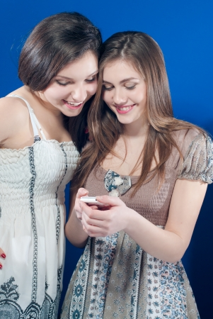 Two happy smiling teenage girls reading mobile message studio blue screen Stock Photo - 17638529