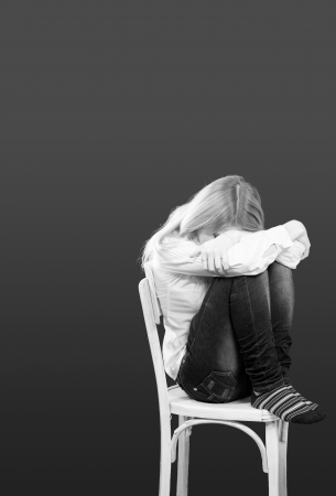 Young woman sitting on chair in depression with empty space Stock Photo - 17575587
