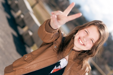 Happy smiling teenage girl showing two fingers or victory sign photo
