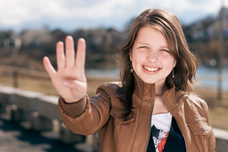Happy smiling teenage girl showing four fingers photo