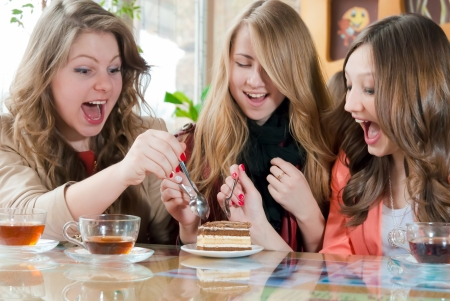 Three happy teenage friends sharing a peice of cake