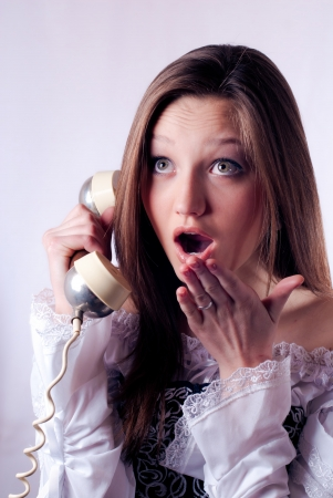 Young beautiful woman calling on retro phone and looking amazed photo