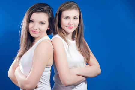 Two young happy women standing back to back over bluescreen Stock Photo - 17547612