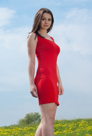 Young pretty woman in red dress against blue sky photo