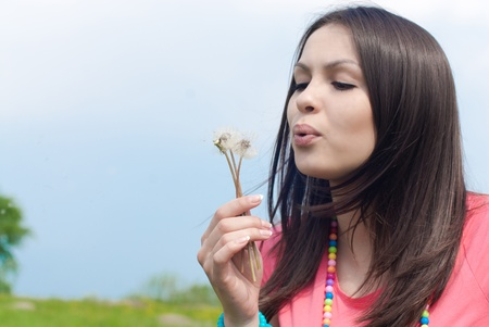 Young beautiful woman blowing on dandelion flower Stock Photo - 17577056