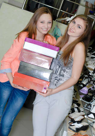 Two happy young women holding boxes of shoes photo