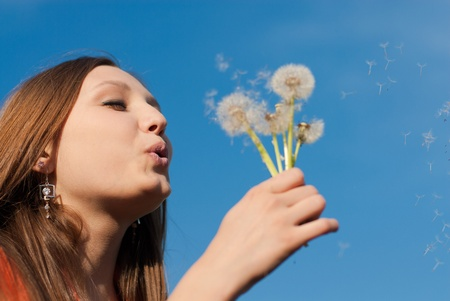 Young beautiful woman blowing on dandelion flower photo
