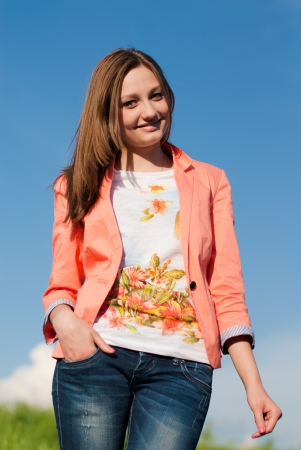 Young pretty woman in pink jacket against blue sky photo