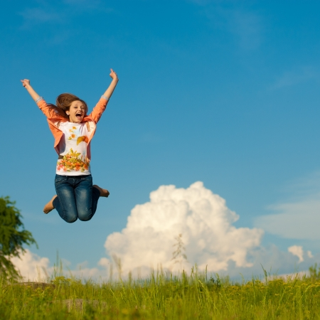 Young pretty woman in pink jacket jumping against blue sky photo
