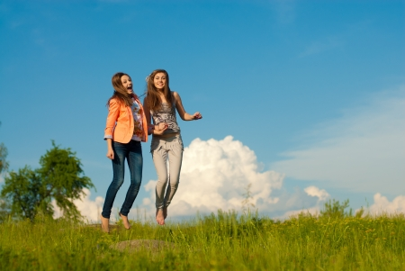 Two young happy women jumping against blue sky photo