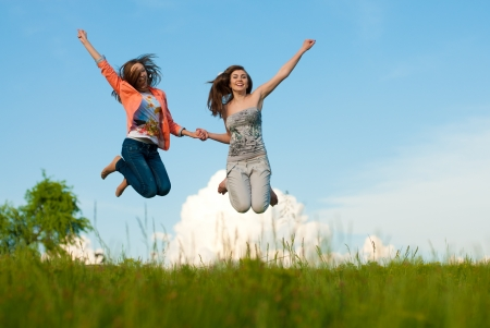 Two young happy women jumping against blue sky Stock Photo