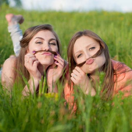 Two happy teenage girl friends lying in green grass Imagens
