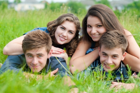Happy four teenage friends lying in green grass photo