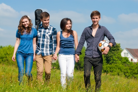 Happy four teenage friends walking together along green field