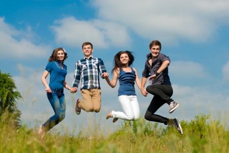 best friends: Happy four teenage friends jumping against blue sky