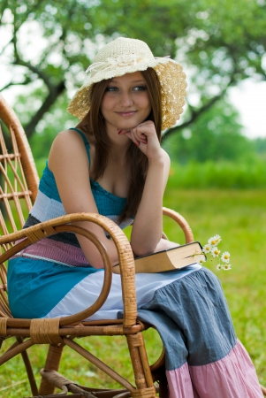 Happy young woman in reading garden chair photo