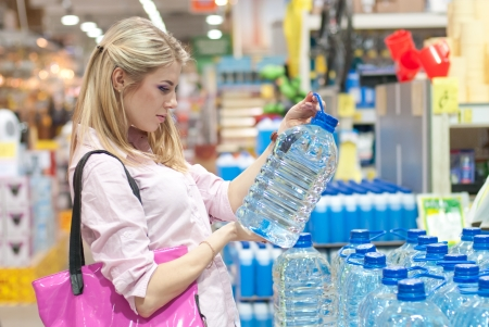 Beautiful young woman buys a huge bottle of water in the store photo