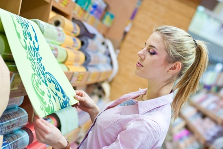 decorator: Young beautiful blond woman choosing among rolls of wallpaper in shop