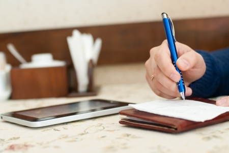 Businessman in restaurant waiting and writting down ideas on napkin though having digital tablet Stock Photo - 17819934