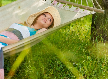 Happy young woman in garden hammock photo