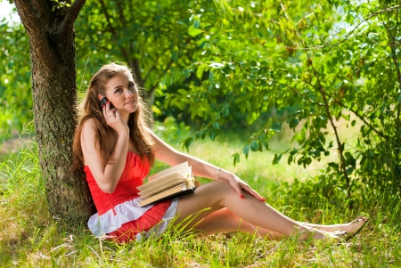 Young woman speaking on mobile in park on sunny day photo