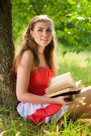 Young woman reading book in park on sunny day photo