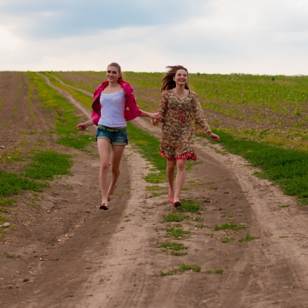 Two happy teen girls running on country road photo