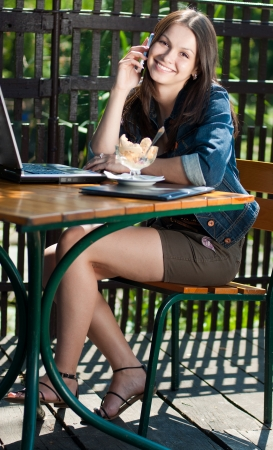 Young happy beautiful woman spaking on mobile in cafe with notebook Stock Photo - 17850632