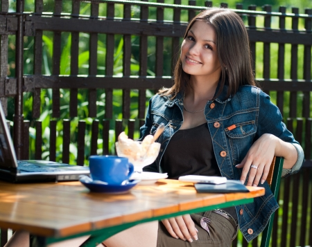 Young happy beautiful woman spaking on mobile in cafe with notebook Stock Photo
